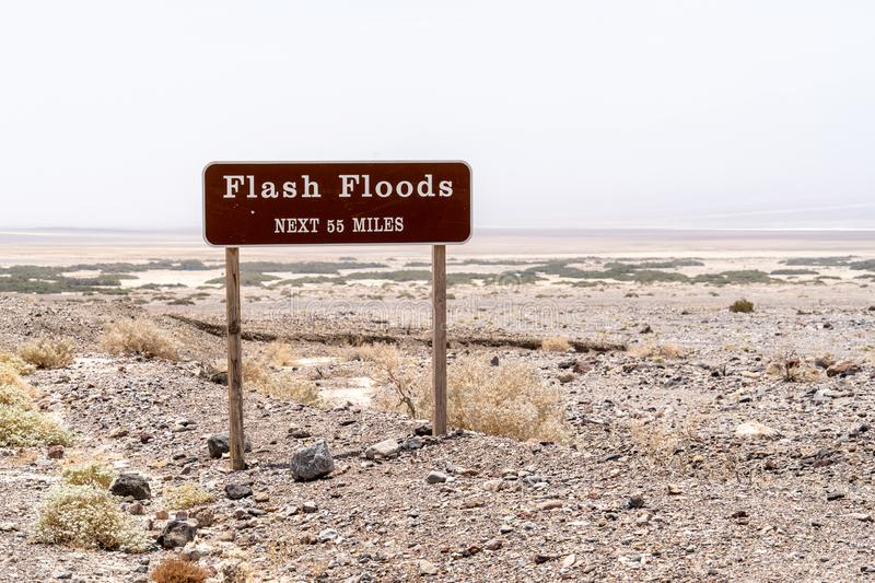 Flash Floods warning sign warns motorists of potential dangerous flooding on roads during rain and monsoon season in California`s stock photos