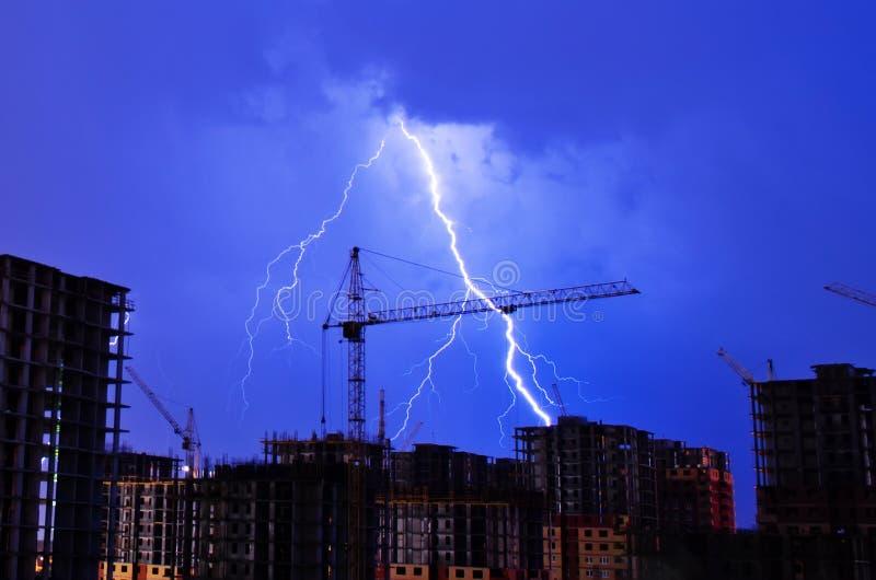 Flash industriale di notte della costruzione di edifici della città del tempo della gru del temporale fotografie stock