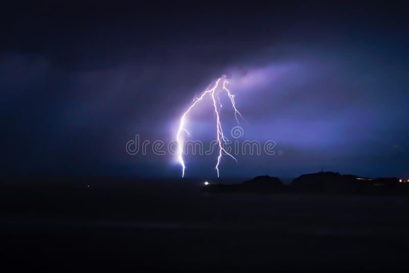 Flash of lightning on a cloudy day at night time over the sea stock images