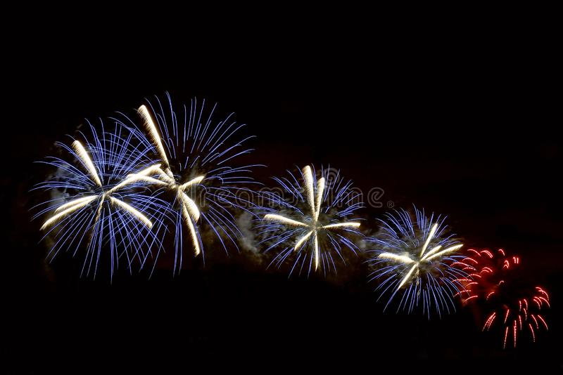 Flashes of blue, white and red festive fireworks stock photo
