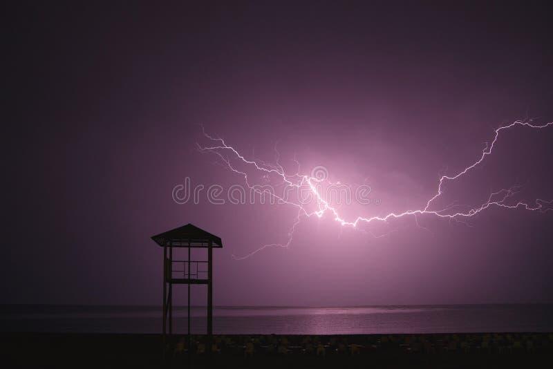 Flashes de foudre à travers le ciel nocturne sur la plage couleur violette Concept de temps dans les lieux de villégiature images libres de droits