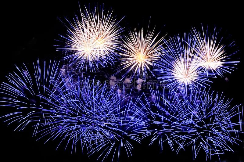 Flashes of fireworks of blue and white colors. Against the black sky background stock image