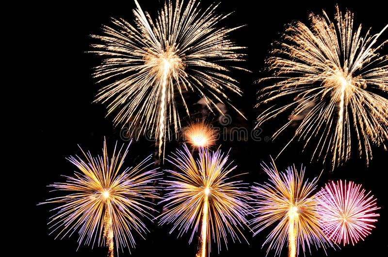 Flashes of fireworks of white, yellow, pink and blue colors stock photography
