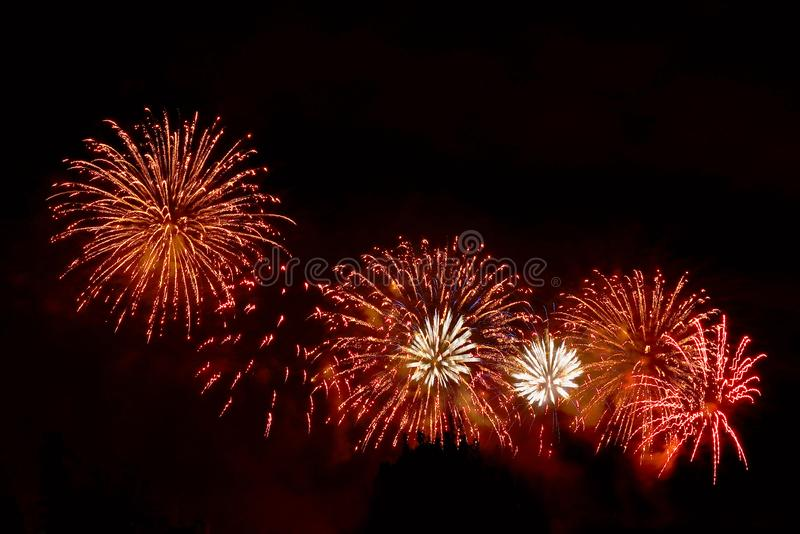 Flashes of orange and white fireworks against black sky royalty free stock images
