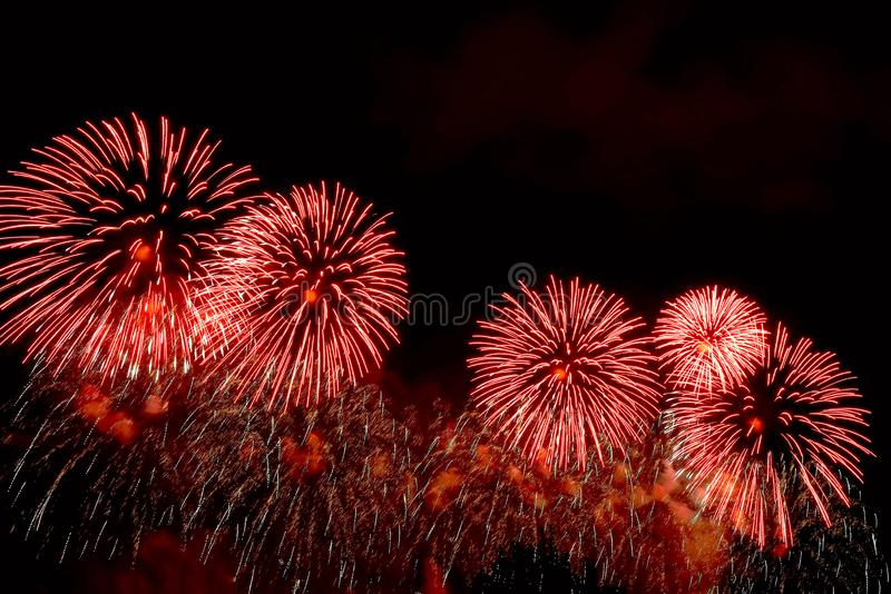 Flashes of red fireworks and white sparks against black sky royalty free stock images