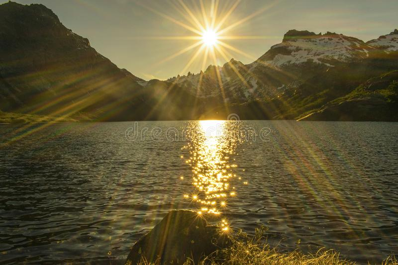 Flashes of sun over a lake. You can see the sun`s rays on a lake between mountains covered by forest stock image