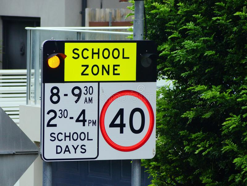 Flashing School Zone Warning Sign, Sydney, Australia. A flashing road sign indicating the beginning of a speed restricted school zone, and the hours when the 40 royalty free stock images