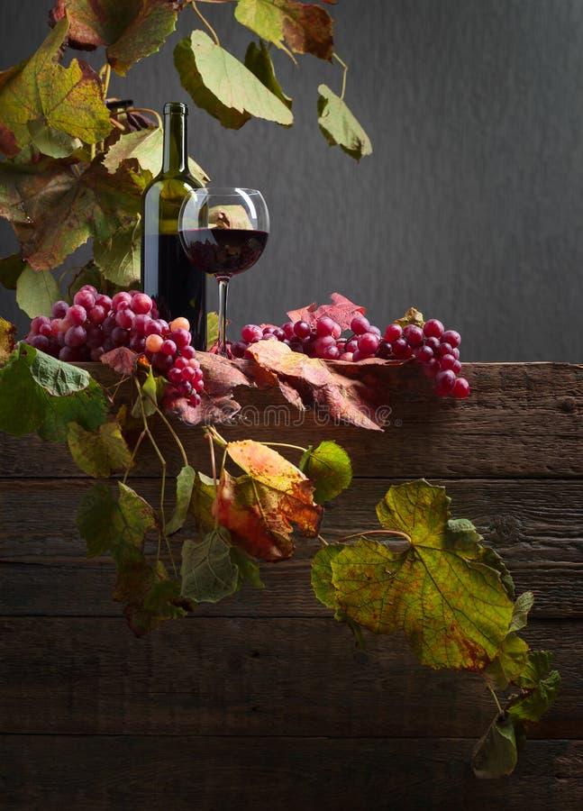 Flask- och exponeringsglasrött vin med druvor på en gammal trätabell royaltyfri bild