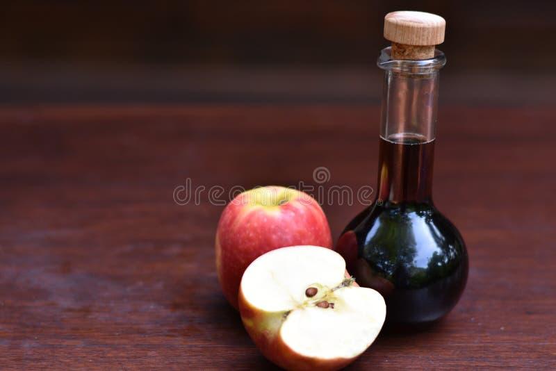 Flaska av äppelcidervinäger bredvid mogna äpplen royaltyfri fotografi