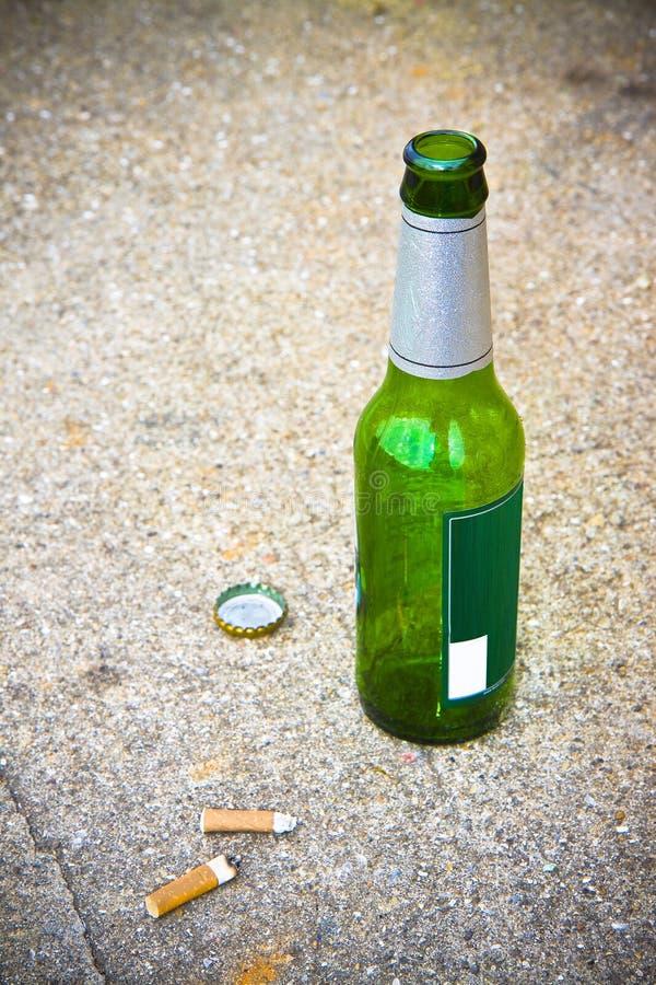 Flaska av öl som vilar på jordningen med tre cigaretts ände royaltyfri foto