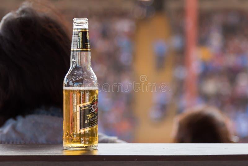 Flaska av öppnat öl som vilar på avsatsen i arena arkivfoto