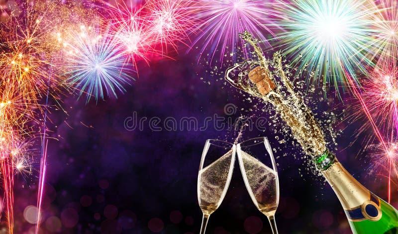 Flaska av champagne med exponeringsglas över fyrverkeribakgrund royaltyfri bild