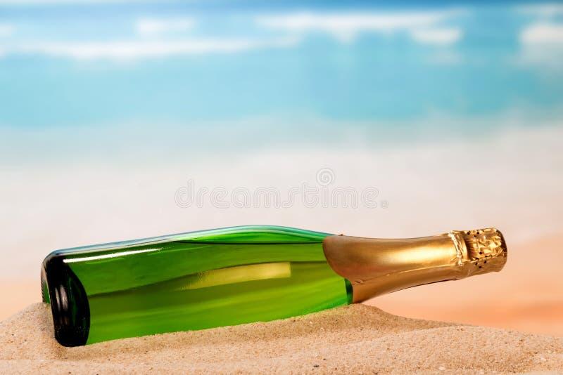 Flaska av champagne på sand royaltyfri foto