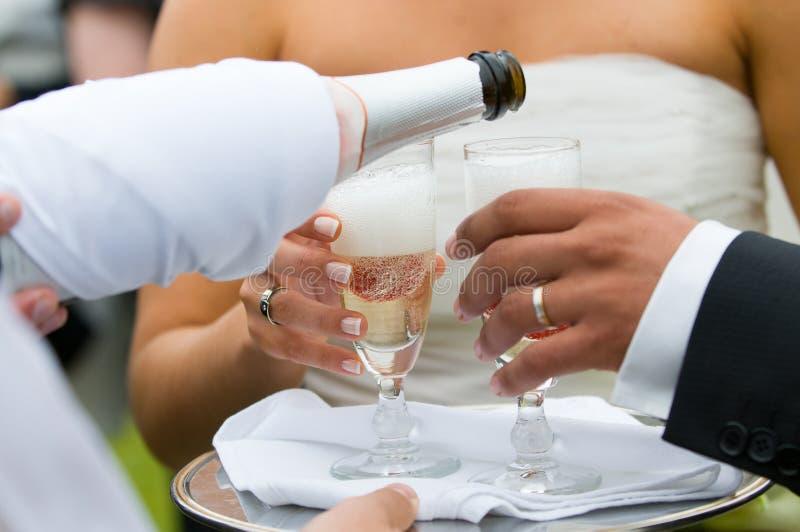Flaska av champagne som in pooring till exponeringsglas arkivfoton