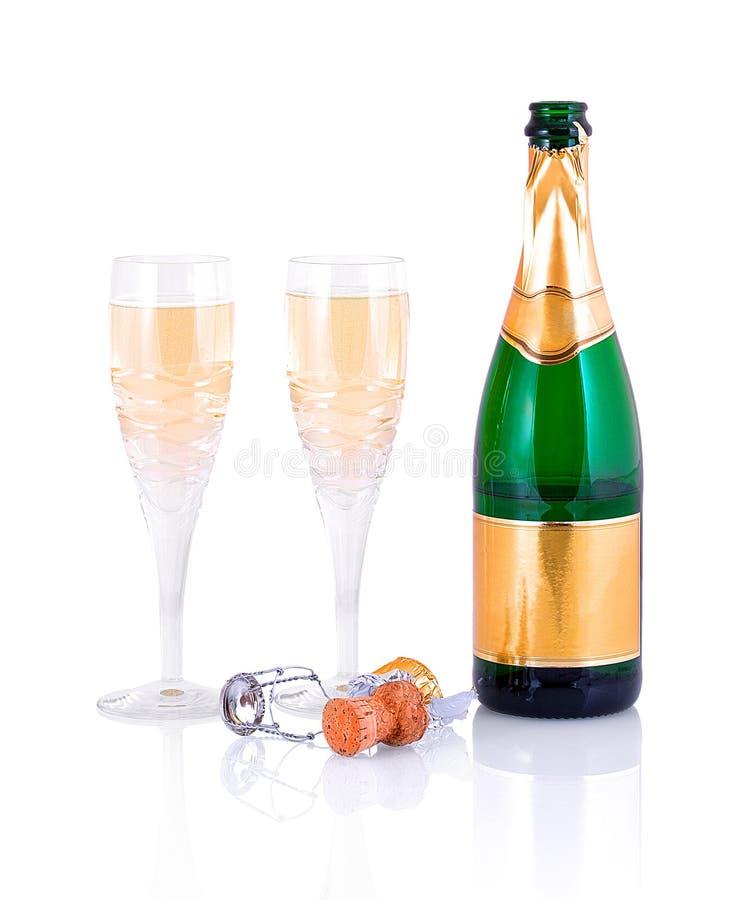 Flaska av champagne, två crystal exponeringsglas och en korkpropp som isoleras på vit bakgrund med skuggareflexion royaltyfria bilder