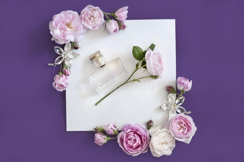 Flaska av doft för kvinna` s på den violetta bakgrunden fotografering för bildbyråer