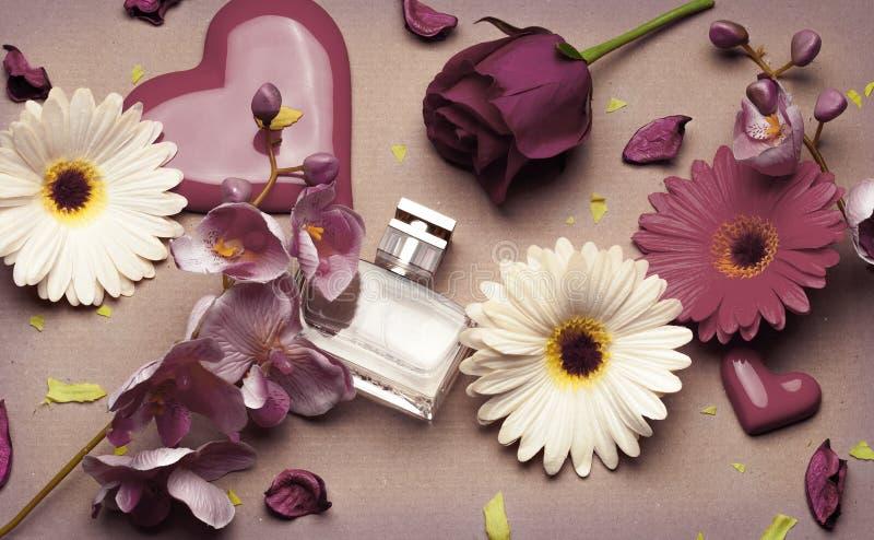 Flaska av doft för kvinna` s på ett ljus - brun bakgrund arkivfoton