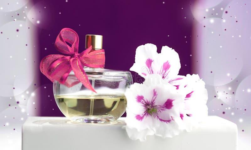 Flaska av doft, violets, på en rosa bakgrund royaltyfria bilder