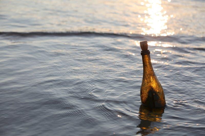 flaska av exponeringsglas på vattnet på soluppgång arkivbild