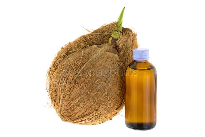 Flaska av förkylning - pressande kokosnötolja bredvid gammal mogen rå coconu royaltyfri foto