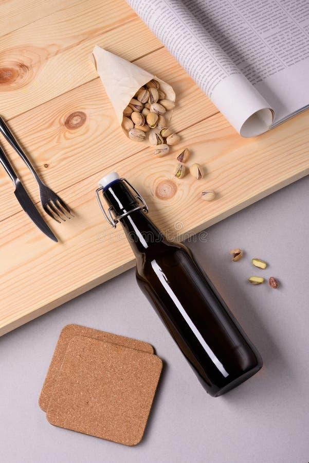 Flaska av hantverköl, pistaschmuttrar och tidningen på wood bakgrund arkivbild