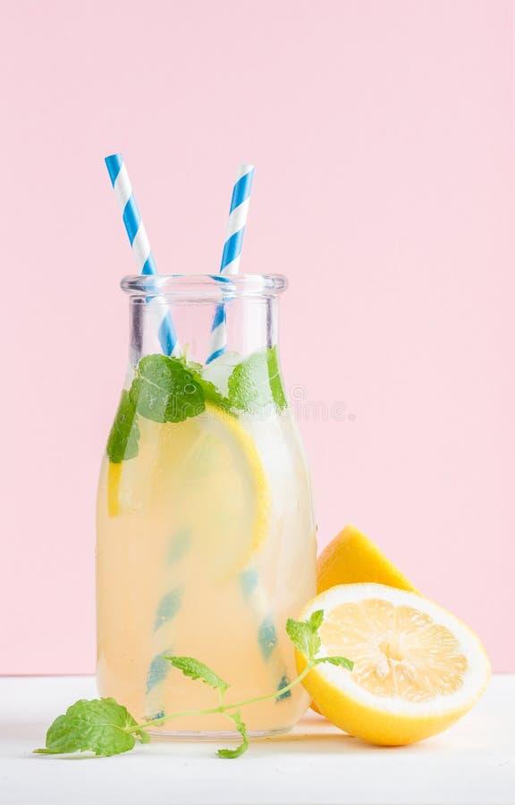 Flaska av hemlagad lemonad med mintkaramellen, is, citroner, pappers- sugrör och bakgrund för pastellfärgade rosa färger fotografering för bildbyråer