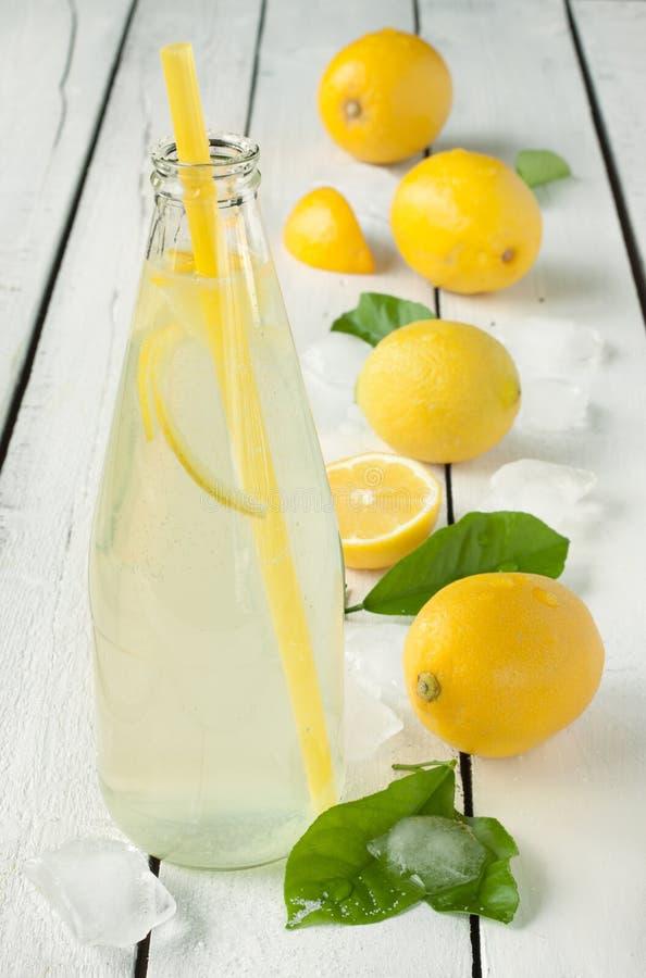 Flaska av lemonad med citroner, is och sidor arkivbilder