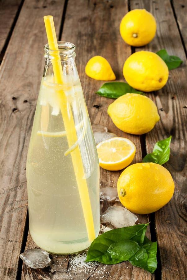 Flaska av lemonad med citroner, is och sidor royaltyfri foto
