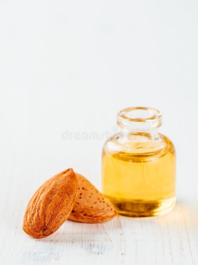 Flaska av mandelolja och mandlar som isoleras på vit bakgrund arkivfoton