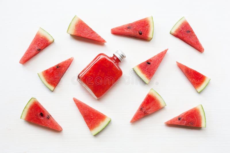 Flaska av ny vattenmelonfruktsaft med vattenmelonstycken arkivfoton