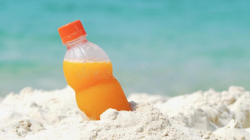 Flaska av orange fruktsaft på stranden royaltyfria bilder