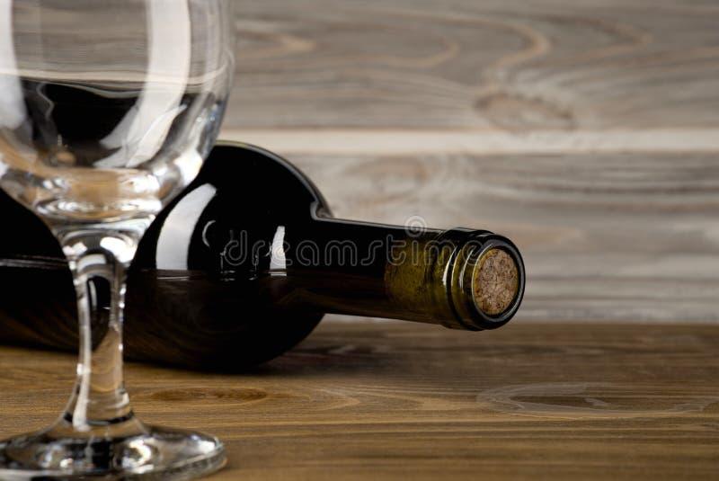 Flaska av rött vin med ett exponeringsglas och en korkskruv på en gammal trätabell royaltyfria foton