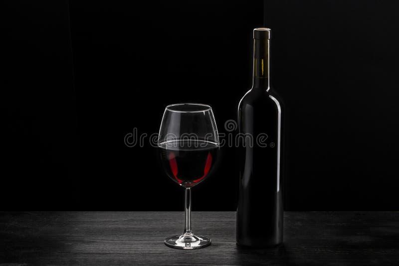Flaska av rött vin och en exponeringsglashalva som fylls med rött vin, på en träsvart tabell, svart bakgrund arkivbilder
