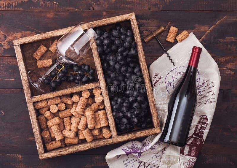 Flaska av rött vin på trä med tomt exponeringsglas med mörka druvor med korkar och korkskruvet inom tappningträasken på mörkt trä arkivbild