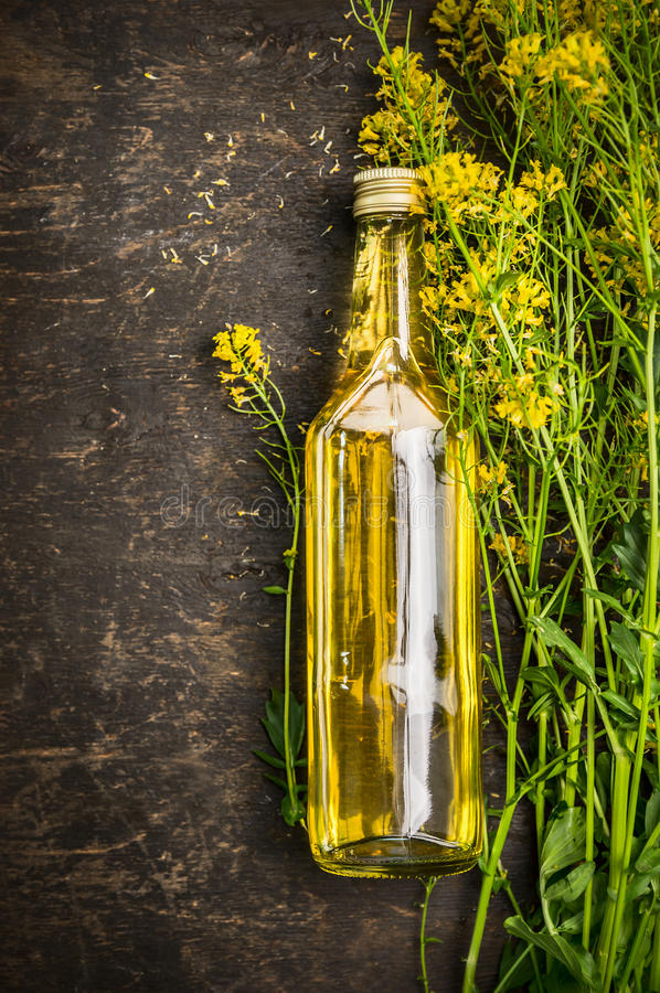 Flaska av Rape olja på lantlig träbakgrund arkivfoton