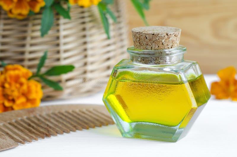 Flaska av skönhetsmedelolja med ringblommablommor extrakt och trähårhårkammen (Tagetes blommar tinktur, avkoken), royaltyfria foton