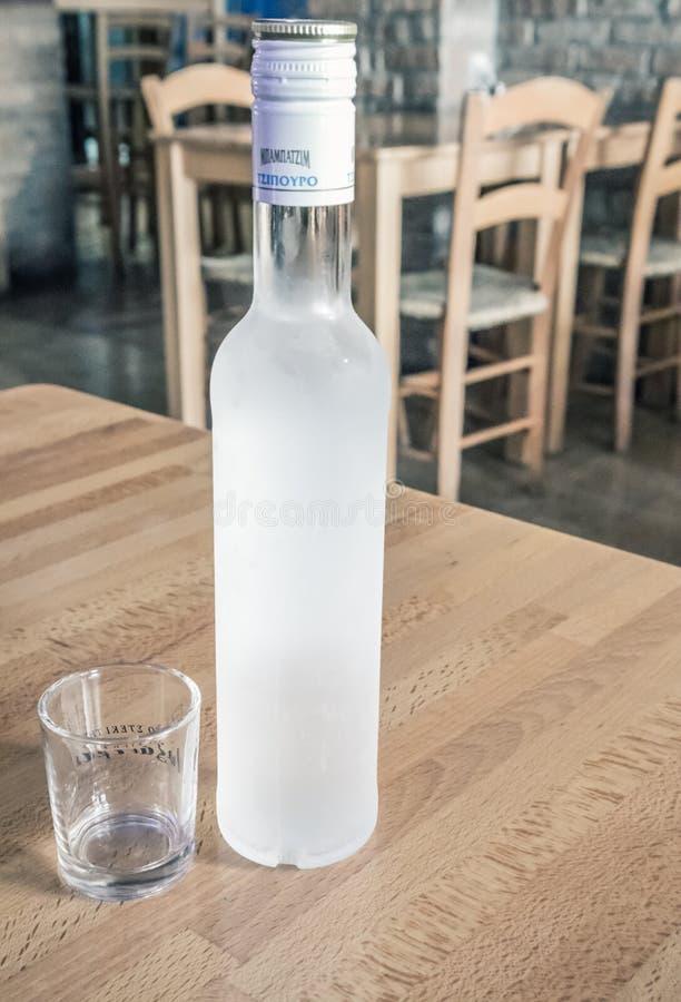 Flaska av tsipouro med skjutit exponeringsglas arkivbilder