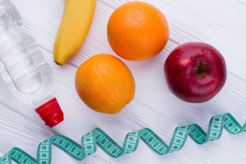 Flaska av vatten, banan, apelsiner och mätaband arkivbild