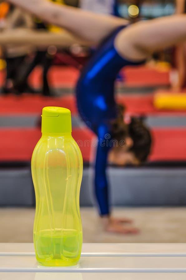 Flaska av vatten för liten gymnastflicka arkivbilder