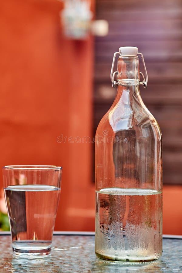 Flaska av vatten med exponeringsglas på tabellen och röd och brun bakgrund royaltyfri fotografi