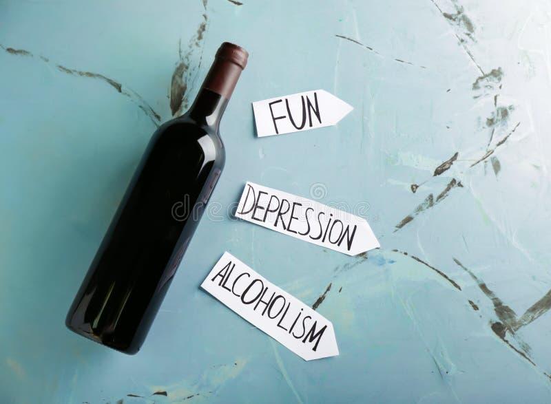 Flaska av vin med ord GYCKEL, FÖRDJUPNING och ALKOHOLISM på färgbakgrund arkivfoto