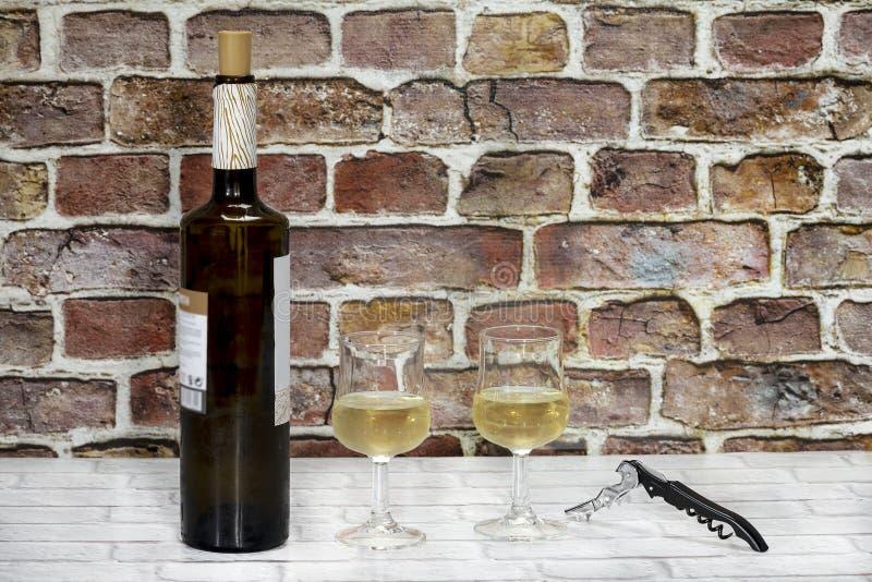 Flaska av vin med två exponeringsglas av vitt vin och en korkskruv fotografering för bildbyråer