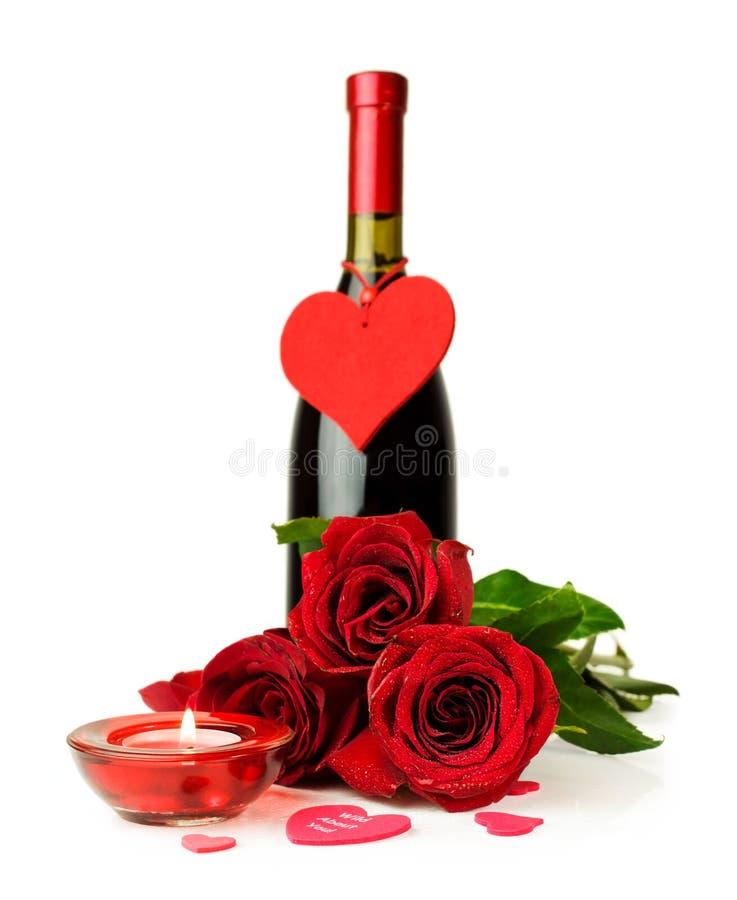 Flaska av vin, röda rosor och stearinljuset arkivbild