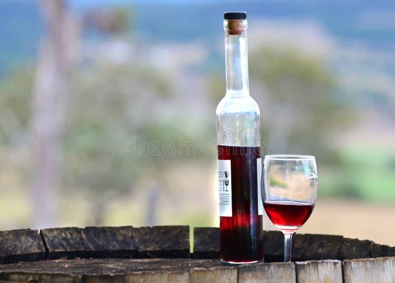 Flaska & exponeringsglas för stillebenrött vinport på den wood trumman royaltyfri bild