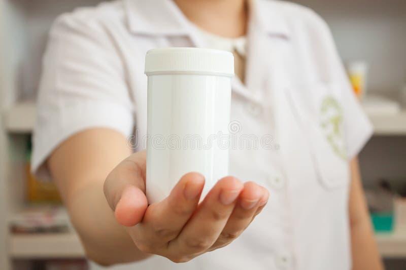 Flaska för apotekarevisningmedicin på hennes hand i apoteket arkivfoto
