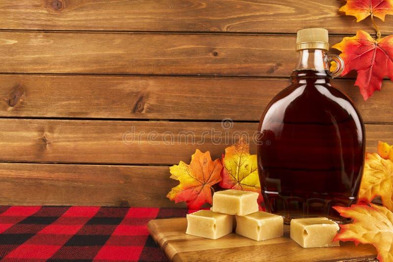 Flaska för lönnsirap på en träplanka Lönnlöv i garnering fotografering för bildbyråer