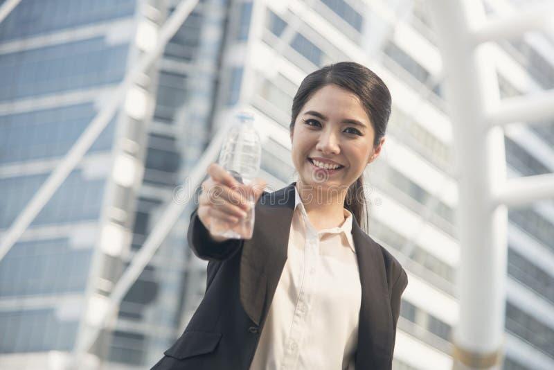 Flaska för vatten för show för ung asiatisk affärskvinna för stående stilig fotografering för bildbyråer