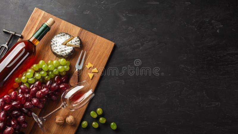 Flaska f?r vitt vin, grupp av druvor, ost och vinglas p? tr?br?de och svart bakgrund arkivbild