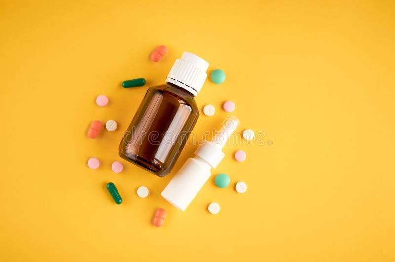 Flaska f?r nasal sprej med pillersammans?ttning, vit mallflaska p? gul bakgrund royaltyfria bilder