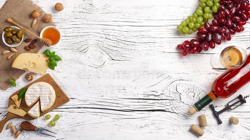 Flaska f?r vitt vin, druva, honung, ost och vinglas p? det vita tr?br?det royaltyfria bilder